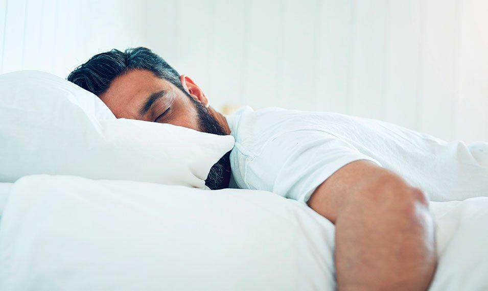 Hombre dormido en la cama. Bruxismo. Rechinar dientes al dormir.